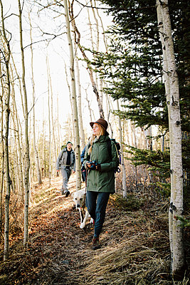Couple with dog hiking in woods - p1192m2093995 by Hero Images