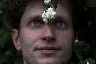 Junger Mann mit Schneebeerenfrüchten vor der Stirn - p1650m2231576 von Hanna Sachau