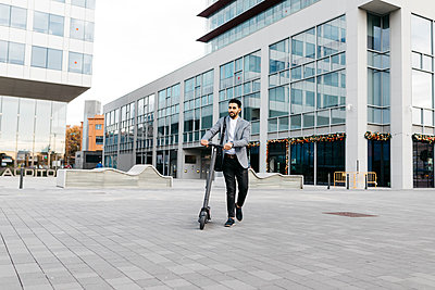 Casual young businessman pushing electric scooter in the city - p300m2160567 by Josep Rovirosa