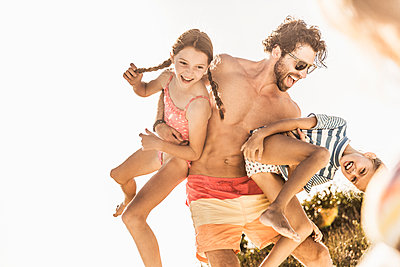 Father having fun with his daughters outdoors in summer - p300m2167507 by Floco Images