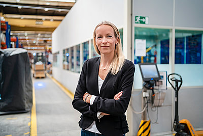 Smiling blond businesswoman with arms crossed standing in industry - p300m2240305 by Daniel Ingold