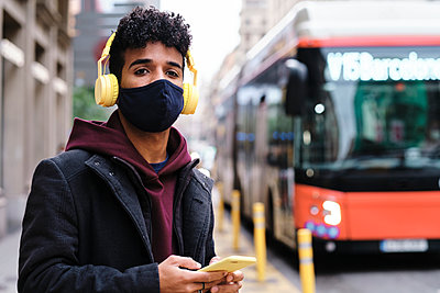 Man wearing protective face mask listening music through headphones while waiting on street in city - p300m2250155 by Alvaro Gonzalez