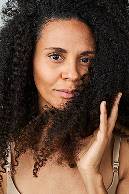 Beautiful woman with hand in curly hair - p300m2264662 by Annika List