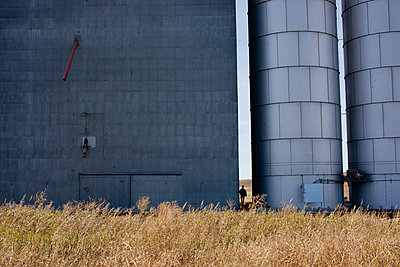 Man Standing Between Grain Storage Building and Metal Silos - p694m872334f by Glasshouse