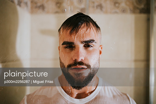 Bearded wet man with t-shirt taking shower in bathroom at home - p300m2256287 by Miguel Frias