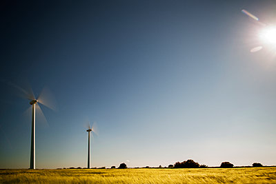 Wind turbines on field against clear sky - p1166m1150358 by Cavan Images