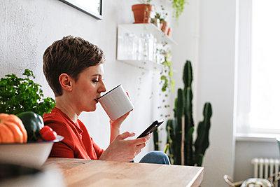 Woman sitting in kitchen, drinking coffee and checking smartphone messages - p300m1587780 von Florian Küttler