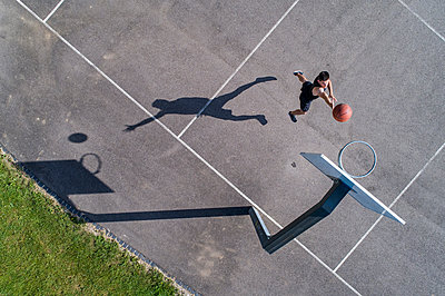 Aerial view of young man playing basketball - p300m2114916 by Stefan Schurr