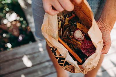 Person holding paper bag with food craps - p312m2249615 by Kajsa-Stina Romin