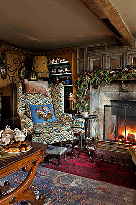 Wingback armchair at lit fir in drawing room of Cheltenham country home - p349m790917 by Polly Eltes