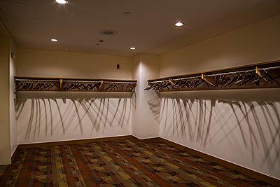 Garderobenraum mit leeren Kleiderbügeln - p397m2015259 von Peter Glass