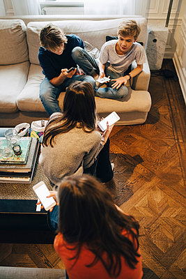 High angle view of friends using smart phone while sitting in living room - p426m1555902 by Maskot