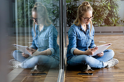 Portrait of young blond businesswoman wearing glasses, sitting on floor, reading. - p924m2165413 by suedhang photography