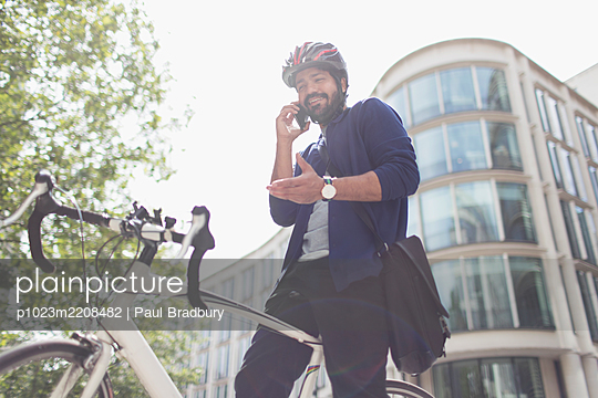 Businessman with  bicycle talking on smart phone in sunny city - p1023m2208482 by Paul Bradbury