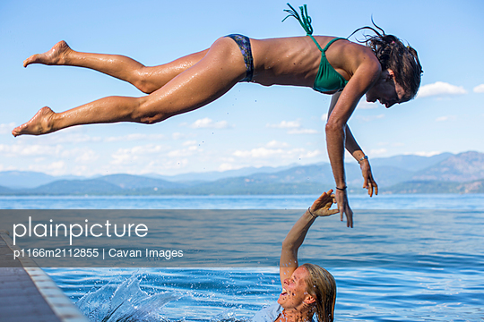 Two adult women playing on a dock in a lake during summertime. - p1166m2112855 by Cavan Images