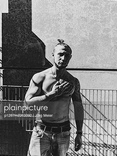 Man with tattoos on bare chest in the sunlight - p1267m2263392 by Jörg Meier