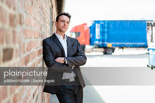 Businessman leaning against brick wall - p300m2102988 by Daniel Ingold