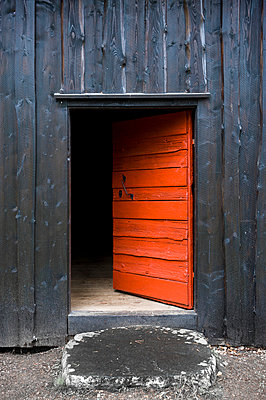 Entrance of an abandoned open red door - p1025m780519f by Björn Andrén