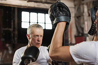 Determined senior male boxer practicing with friend in gym - p1166m1150923 by Cavan Images