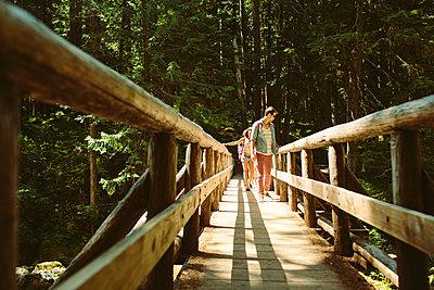 Friends walking on footbridge in forest - p1166m1423033 by Cavan Images
