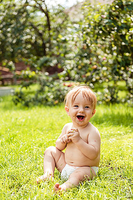 Little boy siting on the grass and laughs - p1166m2157116 by Cavan Images