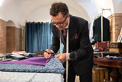 Mature dressmaker comparing cloth samples - p1166m2261412 by Cavan Images