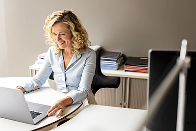 Smiling businesswoman with laptop sitting at desk in office - p300m2267112 by Peter Scholl