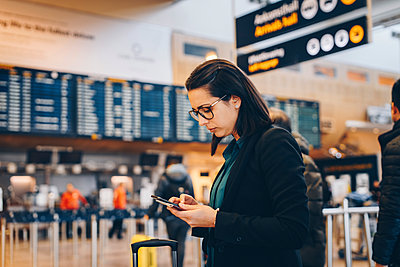 Side view of mid adult businesswoman using mobile phone in airport terminal - p426m1580054 by Maskot