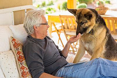 Caucasian man petting dog on patio - p555m1304152 by Marc Romanelli