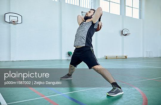 Man with basketball, stretching, indoor - p300m1587002 von Zeljko Dangubic