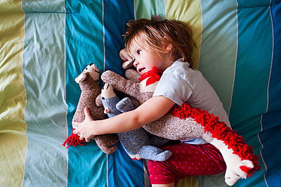 Overhead view of girl with stuffed toys lying on bed at home - p1166m1474193 by Cavan Images