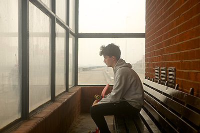 Teenage Boy in Seafront shelter with Skateboard - p1304m1144270 by MY MY