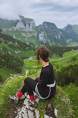 Woman sitting on rock by mountains in Appenzell, Switzerland - p1427m2163648 by Oleksii Karamanov