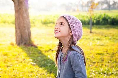 Portrait of smiling girl standing on a meadow in autumn looking up - p300m2080865 by Larissa Veronesi