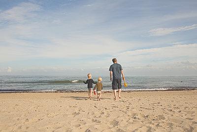 Father with two kids on the beach - p300m2103130 von Irina Heß