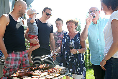 Family having barbecue - p312m2145436 by Helena Christerdotter
