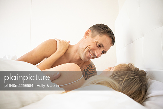 Couple in love embracing in bed - p1640m2259584 by Holly & John
