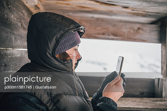 Austria, Kitzbuehel, young woman in raised hide looking at cell phone in winter - p300m1581745 von Gustafsson