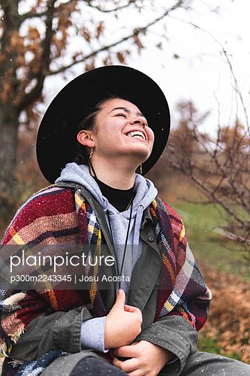 Smiling teenage girl in hat in Autumn landscape - p300m2243345 by Josu Acosta