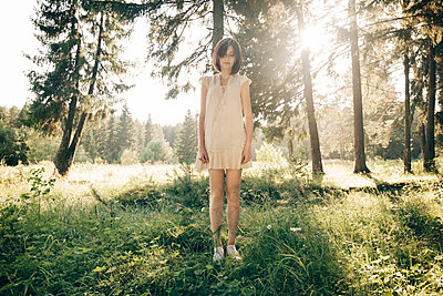 Full length of sad young woman standing on grassy field in forest - p1166m2025096 by Cavan Social