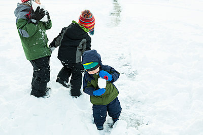 Three brothers play outside making snowballs after winter storm - p1166m2112806 by Cavan Images