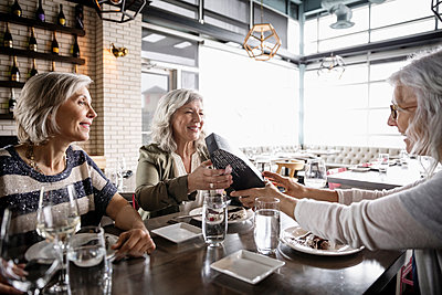 Senior women friends enjoying birthday lunch in restaurant - p1192m2105333 by Hero Images