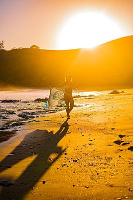 Frau tanzt am Strand bei Sonnenuntergang - p1455m2203706 von Ingmar Wein