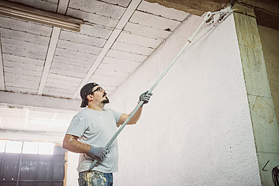 Man painting wall in a garage - p300m1191811 by Jaen Stock