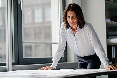 Businesswoman working in office, looking at blueprints - p300m2029798 von Kniel Synnatzschke
