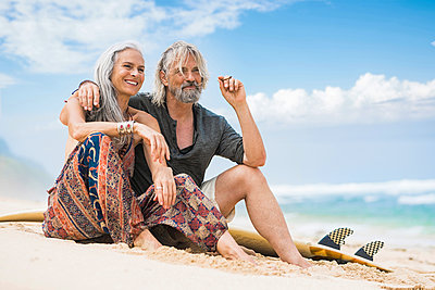 Portrait of senior hippie couple with surfboard relaxing on the beach - p300m2083973 by Steve Brookland