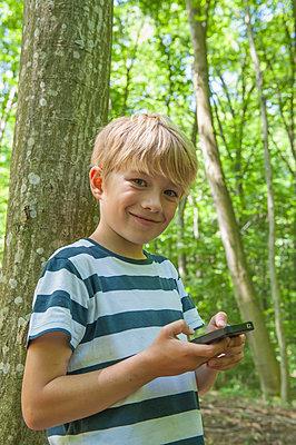 Germany, Bavaria, Munich, Portrait of boy with geocaching, smiling - p300m2207315 by Nico Hermann