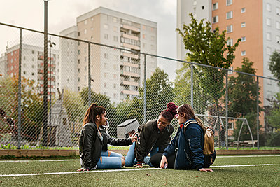 Teenage girls using smart phone on tennis court - p352m2121005 by Folio Images