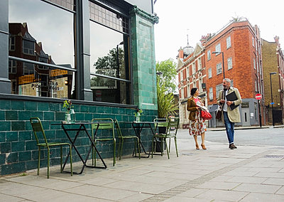 Friends walking by pavement cafe, London, UK - p429m2050796 by Seb Oliver