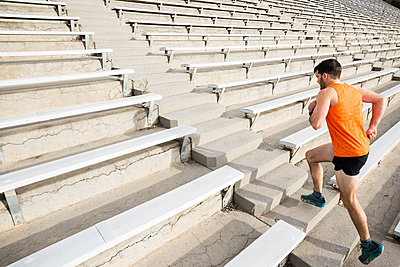 Young male runner running up stadium stairway - p924m2074415 by JFCreatives